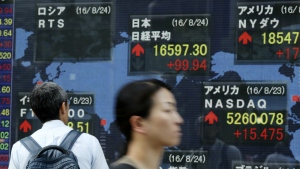 A man looks at an electronic stock board showing world market indexes at a securities firm in Tokyo, Japan on Wednesday, Aug. 24, 2016. (AP / Eugene Hoshiko)
