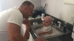 """Trooper Derek Graham, a father of four, said the """"dad instinct"""" took over when he removed the baby's soiled diaper, put him in a sink and began to bathe him. (Source: Derek Graham, West Virginia State Police)"""