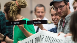 A demonstrator holds up the name plates of two of the commissioners as they disrupt the National Energy Board public hearing into the proposed $15.7-billion Energy East pipeline project proposed by TransCanada, in Montreal, Monday, Aug. 29, 2016. (Paul Chiasson / THE CANADIAN PRESS)