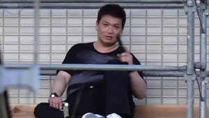 Yasuhide Mizobata, a murder suspect, holding guns sits on scaffoldings as he holes up at an apartment in a standoff after he fired at a police car and escaped, in Wakayama, central Japan, Wednesday, Aug. 31, 2016. (Ren Onuma/Kyodo News via AP)