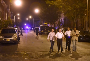 Baltimore police, from left, Deputy Commissioner Dean Palmere, Commissioner Kevin Davis, Stanley Brandford, chief of detectives, and T.J. Smith, police spokesman, walk at a scene where multiple people were shot and wounded in Baltimore, Saturday night, Sept. 24, 2016. (AP / Steve Ruark)