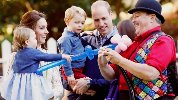 Prince William, Catherine, Duchess of Cambridge, Prince George and Princess Charlotte watch as a man inflates balloons at a children's party at Government House in Victoria, Thursday, September 29, 2016. THE CANADIAN PRESS/POOL-Chris Wattie