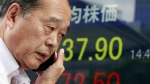 A man uses a mobile phone in front of an electronic stock indicator of a securities firm in Tokyo on Thursday, Sept. 29, 2016. (AP / Shizuo Kambayashi)