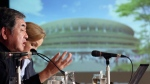 Japanese architect Kengo Kuma, left, speaks about his design of the 2020 Tokyo Olympics stadium, background, on Jan. 15, 2016. (Eugene Hoshiko / AP)
