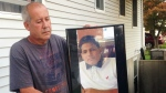 Abraham Chaparro, holds a photograph of his murdered stepson, Miguel Garcia-Moran, outside his home in Brentwood, N.Y. on Sept. 27, 2016. (AP / Claudia Torrens)