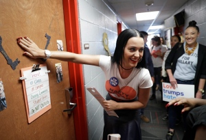 Singer Katy Perry covers the peephole of a dorm room door after knocking on it while canvassing for Democratic presidential nominee Hillary Clinton in a dorm at UNLV, Saturday, Oct. 22, 2016, in Las Vegas. (AP Photo/John Locher)