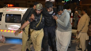 A Pakistani volunteer and a police officer rush an injured person to a hospital in Quetta, Pakistan after two separate attacks in Pakistan on Monday, Oct. 24, 2016. (AP / Arshad Butt)