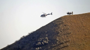 Three people on horseback watch from a hillside as a helicopter sweeps near the New Camp on Pipeline Easement in southern Morton County, N.D. on Wednesday, Oct. 26, 2016. (Tom Stromme / The Bismarck Tribune)