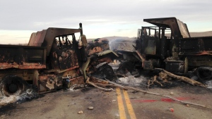 The burned hulks of heavy trucks sit on Highway 1806 near Cannon Ball, N.D., on Oct. 28, 2016. (James MacPherson / AP)