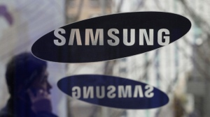 FILE - In this Dec. 12, 2013 file photo, a man passes by the Samsung Electronics Co. logos at its headquarters in Seoul, South Korea. (AP Photo/Ahn Young-joon, File)