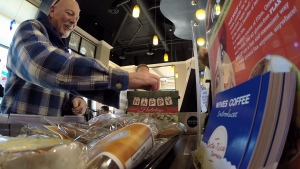 A Waves cafe customer donates to the Share Food Bank after learning CTV was paying for his coffee. (CTV)