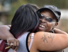 Velma Aiken, the paternal grandmother of Kamiyah Mobley, who was kidnapped as an infant 18 years ago, gets a congratulatory hug from a family member after Mobley was found safe Friday, Jan. 13, 2017, in Jacksonville, Fla. (The Florida Times-Union via AP/Will Dickey)
