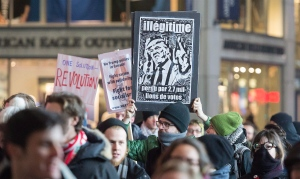 An anti Donald Trump protesters hold up signs during a demonstration in Montreal, Friday, January 20, 2017. (Graham Hughes / THE CANADIAN PRESS)
