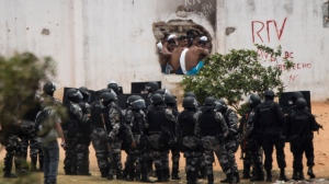 Inmates, top, watch as police officers enter the Alcacuz prison amid tension between rival gangs in Nisia Floresta, near Natal, Brazil, Saturday, Jan. 21, 2017.(AP Photo/Felipe Dana)