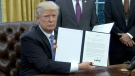 U.S. President Donald Trump holds up a signed memorandum beginning the United States' withdrawal from the Trans-Pacific Partnership.