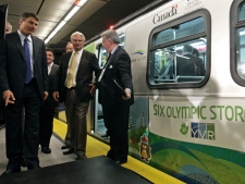Vancouver Mayor Gregor Robinson, left, and British Columbia Premier Gordon Campbell are directed by an aide after riding on the Canada Line rapid transit train's inaugural run from Vancouver International Airport in Richmond, B.C., to downtown Vancouver on Monday August 17, 2009. (THE CANADIAN PRESS/Darryl Dyck)