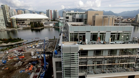 Construction continues on a building at the athletes' village for the Vancouver 2010 Winter Olympic Games in Vancouver, B.C., on Friday October 9, 2009. B.C. Place, which will host the opening and closing ceremonies during the games, is pictured at left in the distance. Media was given a tour of suites in one of the buildings that will house more than 2,800 athletes during the 2010 Winter Olympics. THE CANADIAN PRESS/Darryl Dyck