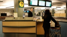 A passenger stops at one of two newly installed information booths set-up in the arrivals area of Vancouver International Airport as part of changes the airport undertook in the wake of the death of Polish immigrant Robert Dziekanski. (THE CANADIAN PRESS file photo/Richard Lam)