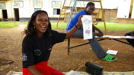 Counsellor Concy Awoto holds up the drawing during an art therapy session at the Children of War Centre in Gulu, Uganda.  (Darcy Wintonyk/CTV)