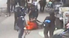 The Vancouver Police Department has launched an investigation after a human rights group released a video showing a beat cop shoving a disabled woman, seen in red, to the ground in Vancouver's impoverished Downtown Eastside. (Handout)