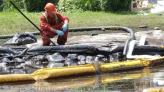 In this July 29, 2010 file photo, a worker monitors water in Talmadge Creek in Marshall Township, Mich., near the Kalamazoo River as oil from a ruptured pipeline, owned by Enbridge Inc., is attempted to be trapped by booms. (AP / Paul Sancya)