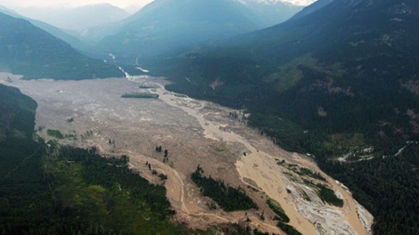 Smoke from wildfires hangs in the air as mud and debris fills a valley along the Lillooet River after a landslide occurred near Meager Creek Hot Springs north of Pemberton, B.C., on Friday August 6, 2010. (CP/Darryl Dyck)