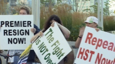 Anti-HST activists hold up signs at a Vancouver event. Aug. 11, 2010. (CTV)