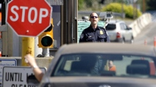 A U.S. Customs and Border Protection officer looks toward a car coming toward him.