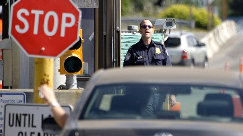 A U.S. Customs and Border Protection officer looks toward a car coming toward him at the border crossing between the U.S. and Canada, in Blaine, Wash. on Saturday, May 30, 2009. (AP / Elaine Thompson)