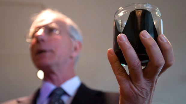 David Black holds a jar of raw bitumen in Vancouver, B.C., on Aug. 17, 2012.