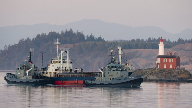 The MV Sun Sea is escorted past Fisgard Lighthouse and into CFB Esquimalt in Colwood, B.C.,Friday, Aug. 13, 2010. (THE CANADIAN PRESS/Jonathan Hayward)