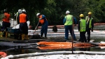 FILE - In this July 30, 2010 file photo, crews clean up oil, from a ruptured pipeline, owned by Enbridge Inc, near booms and absorbent materials where Talmadge Creek meets the Kalamazoo River as in Marshall Township, Mich. Federal investigators are expected to present their findings Tuesday, July 10, 2012 on the likely cause of a pipeline rupture that spilled more than 800,000 gallons of crude oil into the river nearly two years ago. (AP Photo/Paul Sancya, File)